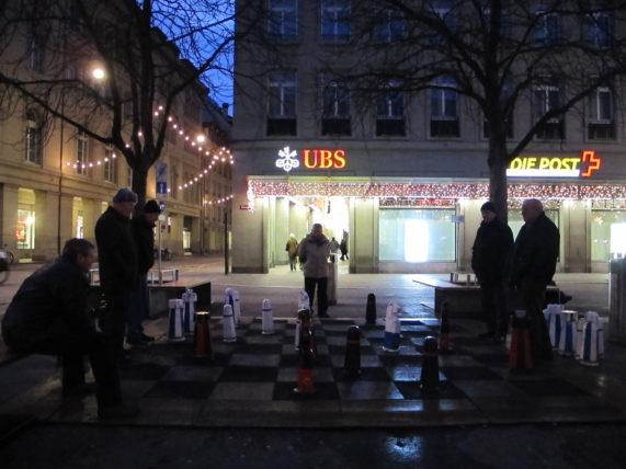 Pessoal jogando xadrez gigante perto do parlamento